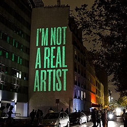 """I'm not a real artist"" is painted in Paris by SpY with phosphorescent paint. After the lights are fully charged, they shine brightly on their own once night falls. Nuit Blanche 2014 - Paris"