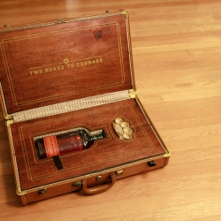 """The two roads to courage."" A suitcase that holds nothing but a bottle of bourbon and a set of brass knuckles."