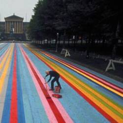 "Artist Gene Davis putting finishing touches on his 414-ft-long painting. ""Franklin's Footpath,"" painted on the street in front of the Philadelphia Museum of Art in 1972. Photo by Henry Groskinsky."