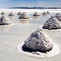 The biggest and highest salt flats in the world, Salar De Uyuni in Bolivia has to be seen to be believed.  Your attention is first drawn to the mysterious mounds of sand that dot the landscape.