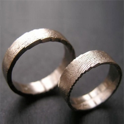 Véra Nováková creates metal jewelry with an organic feel - fingerprints, wood grains, etc are imprinted into her pieces.