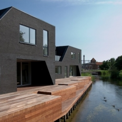 """A-Husene"" housing by Cedra Architects in Grenaa - Denmark. Some truncated black bricks volumes on an artificial island."