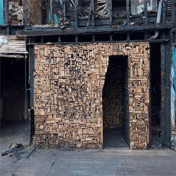 Catie Newell Salvaged Landscape reclaims a building burned by arson in Detroit, MI. Constructed from salvaged pieces of wood from the burned out building, Newell created a passageway through the charred frame.