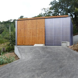 The green Casa em Arruda dos Vinhos by Plano B, with a small footprint, rammed earth walls, structural framing made from wood recycled from the previous building, and a cork board facade.
