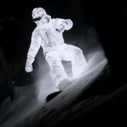 Snowboarder William Hughes glides down through the French snow in a gleaming L.E.D. suit