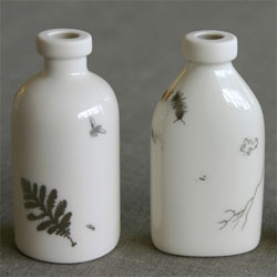 Beautiful porcelain bottles inspired by memories of antique bottles dug up as children. The bottles are embellished with platinum decals of insects, weeds, roots and dirt.