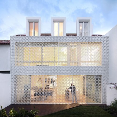 Restelo House by João Tiago Aguiar - A lace-like curtain inspired by traditional Portuguese tiles wraps the rear side of this house in Lisbon.
