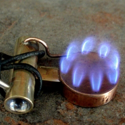 A working stove necklace - hand-crafted brass and copper alcohol burner with a fuel line and tank by Stuart Breidenstein of Go Robot!