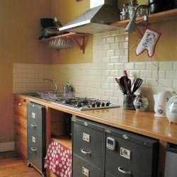Vintage industrial and tiny: A Belgium home kitchen with antique file drawers for storage.