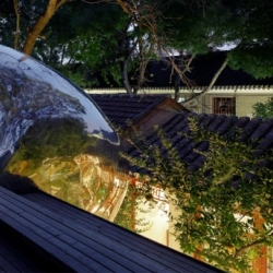 Hutong Bubble 32 is a metallic bubble built in a small courtyard in Beijing.It provides a toilet and a staircase that extends onto a roof terrace for a newly renovated courtyard house.