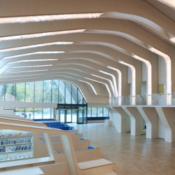 When standing within the cavernous expanse of Norway's new Vennesla Library one is almost transported to the inside of a blue whale, looking up at the arched, ivory ribcage....