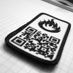 Velcro-backed Commando Nerd patches: each contains a unique QRCode that you control, and others can scan with an iPhone.  Link your jacket to a different YouTube video each day!
