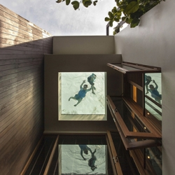 A glance upward from the ground floor reveals a window to the bottom of the rooftop swimming pool at Aamer Architect's Adrian's Garden Villa.