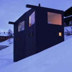 In the Swiss Alps, EM2N Architecture designed this black wood holiday cottage.