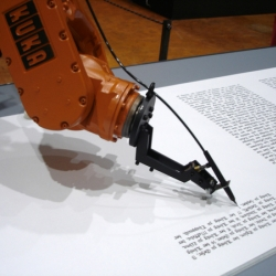 A robotic arm that writes calligraphy is programmed to write out the entire Martin Luther bible on a long roll of paper.