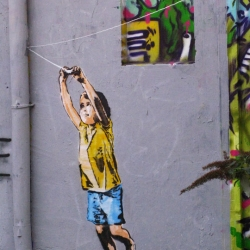 """a new feel good piece from street artist ABOVE done in the streets of Paris,France. The artist took the popular french proverb and used it as the foundation of his """"arrow kite"""" installation."""
