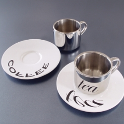 Anamorphic Cups. The stainless steel cup has a polished mirror finish. The porcelain saucer is printed with distorted images or words. Comes in six different words and images.
