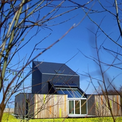 Using untreated larch wood and black fibre cement panels to optimise solar energy gain this house blends with its surrounding. By Peter Kuczia