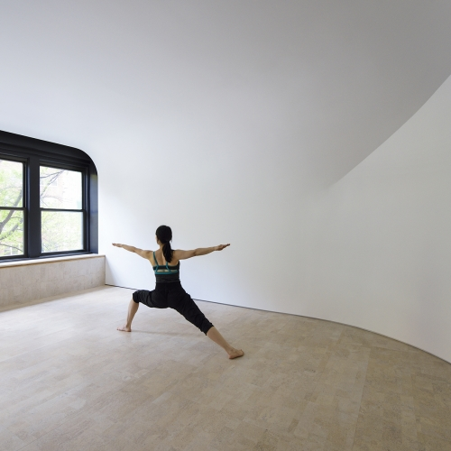 White curved walls merge into a tapered ceiling inside this yoga and meditation studio in New York, designed by Clouds Architecture Office. The project has just received an Honor Award from the AIA.