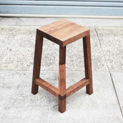 The legless barstool by Josh Carmody uses a diagonal cross brace to offer support and create an optical illusion.