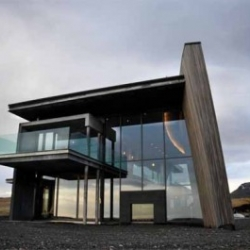 Stunning Casa G Vacation home in Iceland by Gudmunder Jonsson. The house has a curved wooden elevation that is glacier-like in appearance and the home is positioned to offer 4 very different views from each direction.