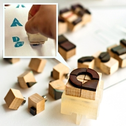 'CREO' by Charissa Rais is a customizable stamping device that could generate geometric letterforms. Comes in a wooden package complete with one stamp holder and a set of little stamp heads.