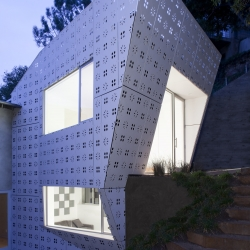 Diamond House is a house extension designed by XTEN Architecture as a patterned and perforated lantern illuminating a California canyon.