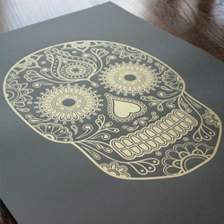 Created in celebration of the Day of the Dead tradition, this sugar skull print is uniquely printed in shining gold ink. designed by London-based medical illustrator Emily Evans.