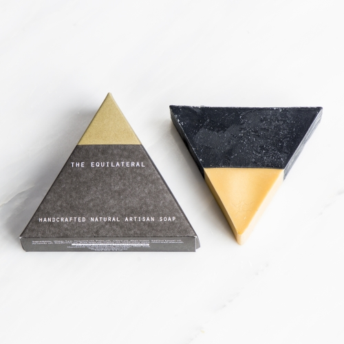Juniper & Scout Black Gold Equilateral Soap. Gold mica-colored top, activated charcoal bottom to deep-clean pores. Scented with lavender and tea tree essential oils. For use on face and body.