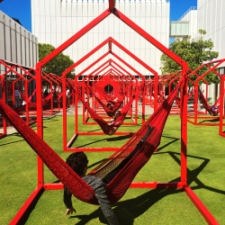 Home is where the hammock is. Woodruff Arts Center, in Atlanta, where 40 red metal frame houses outfitted with hammocks dot the interior piazza. By Esrawe.