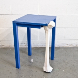 A femur bone is modeled and 3D printed to become a replacement leg for a wooden table. 'Femur table' by Atlanta interdisciplinary designer Kevin Byrd.