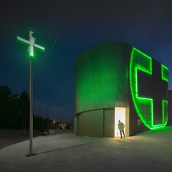Nice pharmacy design with neon symbol incorporated into the façade by José Carlos Cruz.