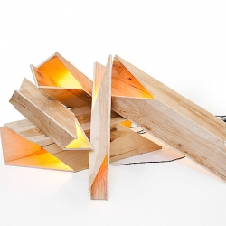 Rafael DeCardena's Firewood Lights – a glowing abstract version of a fireplace. Constructed of angular cut wood, Firewood Lights are internally illuminated with a warm light.