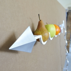 FrecciaMela, a bowl to be fixed to the wall made from iehter Corian or aluminum, with an aluminum tip. Among the fruit and the wall is sandwiched a thin 2mm layer of polycarbonate. Designed by Nicola Loi & Andrea Maffezzoni of a++de.