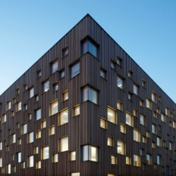 The building appears cubic with large facades and square windows placed in a vibrant, rhythmic sequence on all sides.