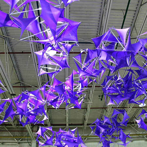 "Virginia Melnyk ""Purple"" is a site specific installation at Echo Art Fair 2016 in Buffalo, New York. The cloud like design is an aggregation of 45 tensegrity modules using acrylic rods and spandex fabric that flutters and shifts  from various view points in the space."