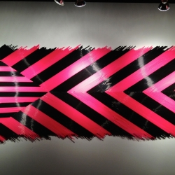 based on the concept of Dazzle Camouflage, Matthew Parker Events created this mural from over 10000 black and pink drinking straws on view at the Viking Gallery at Western Washington University.