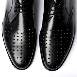 """Left shoe!!! Right shoe!!!,"" by artist Liam Gillick consists of a pair of sleek black leather brogues with perforated holes in the toe-box. Done in collaboration with traveling boutique Clemens en August"