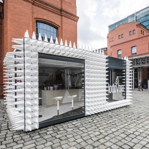 In the Courtyard of Art, mode:lina studio designers approached its façade as if it was a piece of art. Dark walls were extended with the use of almost one thousand white sport cones, referring to LODOVNIA's flagship product – natural ice cream in a cone.