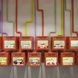 Macarons displayed in 'break glass in case of emergency' boxes, a dessert 'sushi train' and macaron wallpaper inspired by Willa Wonka, from Luchetti Krelle design for the new Adriano Zumbo patisserie in Sydney.