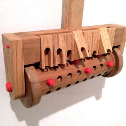 Musical Mower is a wooden interactive musical toy for kids handcrafted by Cynthia Poon. Based on the placement of the red pegs, different notes will sound as the mower rolls around.