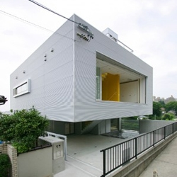 A flying steel covered volume is this house in Nagoya, Japan made by Architecture W. Take a look at the ground floor covered patio with the yellow stairs volume.