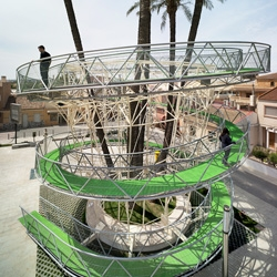 El Mirador del Palmeral designed by Joaquin Alvado Bañon in Spain, serves both as a spiraling walkway/lookout tower and a brace for the palm trees.