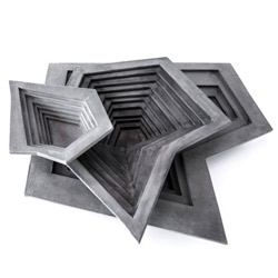 Designer Vidó Nóri removes all porcelain from the table and serves lunch on almost indestructible plates made of concrete, in geometric shapes that resemble tangrams or origami.