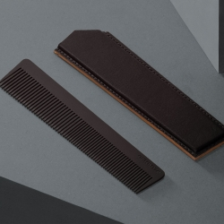 Grade 5 Titanium milled comb with black titanium nitride coating and handmade Veg. tan leather sleeve from Octovo.