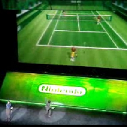 Director and General Manager of Nintendo Shigeru Miyamoto in a silly performace playing tennis on a big screen using the Wii remote, the noises he makes are great.