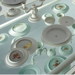 Nymphenburg's Hidden Wealth dinnerware  has a hand-painted pattern on the bottom. The set is sold with a glass-top steel table with a mirror beneath the serving surface, so everyone can see the pattern.