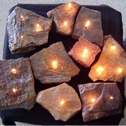 These are beautiful real rocks drilled to hold oil and have wick, so they function as candles or oil lamps. The price is right and they look great outside!