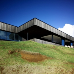 New Zealand's Parihoa House by Andrew Patterson is a modern day castle that rests quietly on a lusciously green windswept hill.