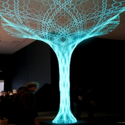 SonUmbra is a beautiful solar-powered tree composed of strands of light-emitting fabric woven into a lucent web of branches.